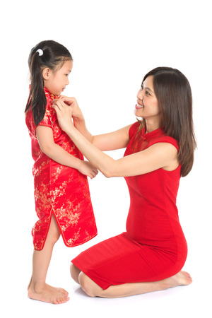 Asian Chinese family preparing for Chinese New Year festival, with traditional Cheongsam
