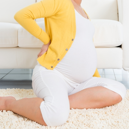 Back pain. 8 months pregnant woman holding her back while sitting on a floor at home.