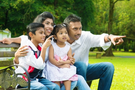 Happy Indian family at outdoor park. Candid portrait of parents and children having fun at garden park. Fingers pointing away.
