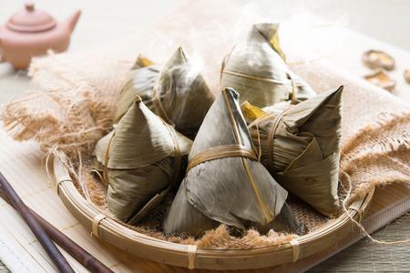 Foto de Asian Chinese rice dumplings on basket, tea at background. - Imagen libre de derechos