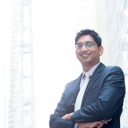 Foto de Portrait of a good looking smiling Indian businessman crossed arms standing at modern building, with natural light. - Imagen libre de derechos
