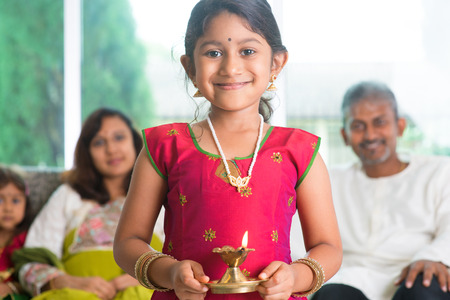 Photo for Indian family celebrate diwali or deepavali at home, little girl with traditional clothing sari, hands holding oil lamp indoor. - Royalty Free Image