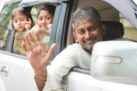 Photo pour Indian family waving hands and saying goodbye, sitting in car ready to trip. Asian family lifestyle. - image libre de droit