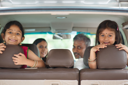 Photo pour Happy Indian family sitting in car smiling, ready to vacation.  Asian parents and children. - image libre de droit