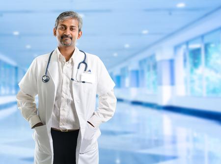 Photo pour Indian doctor. Mature Indian male medical doctor standing inside hospital. Handsome Indian model portrait. - image libre de droit