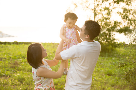 Photo for Happy Asian family playing in meadow during summer sunset, outdoors shot. - Royalty Free Image
