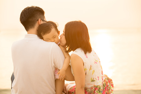 Portrait of young Asian family seated on beach outdoor vacation, during summer sunset, natural sunlight with flare.