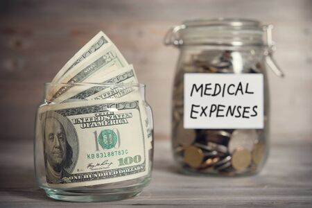 Photo pour Dollars and coins in glass jar with medical expenses label, financial concept. Vintage tone wooden background with dramatic light. - image libre de droit