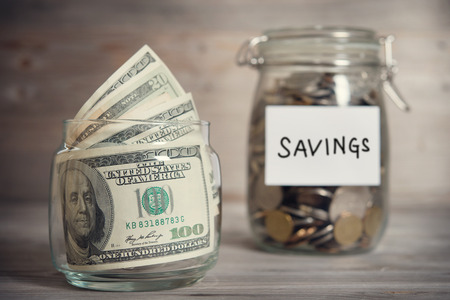 Foto de Dollars and coins in glass jar with saving label, financial concept. Vintage tone wooden background with dramatic light. - Imagen libre de derechos