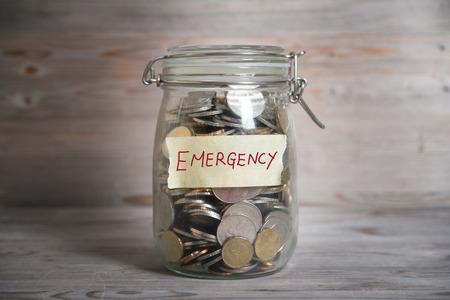 Foto de Coins in glass money jar with emergency label, financial concept. Vintage wooden background with dramatic light. - Imagen libre de derechos