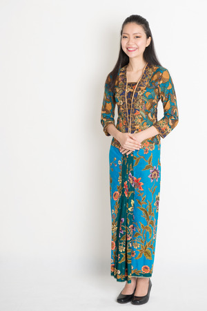 Photo for Full length Southeast Asian female in batik dress standing on plain background. - Royalty Free Image