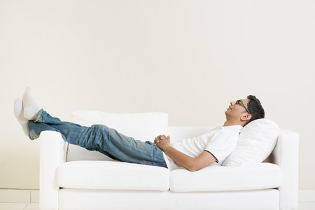 Foto de Indian guy daydreaming and rest at home. Asian man relaxed and sleep on sofa indoor. Handsome male model. - Imagen libre de derechos