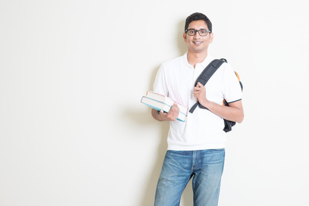 Photo for Portrait of adult Indian university student with books and bag. Asian man standing on plain background with shadow and copy space. Handsome mixed race male model. - Royalty Free Image