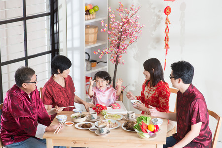 Foto de Celebrating Chinese New Year, reunion dinner. Happy Asian Chinese multi generation family with red cheongsam dining at home. - Imagen libre de derechos