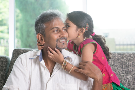 Indian daughter kissing father at home.