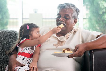 randchild feeding butter cake to grandparent.