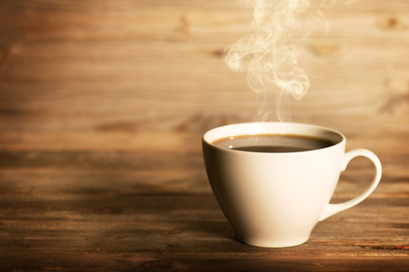 Photo pour Steaming coffee in white cup in soft focus setting with dramatic ambient light, over dark wooden background. - image libre de droit