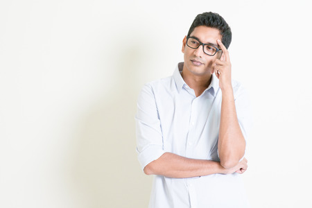 Foto de Portrait of handsome casual business Indian man thinking with serious face expression, standing on plain background with shadow, copy space at side. - Imagen libre de derechos