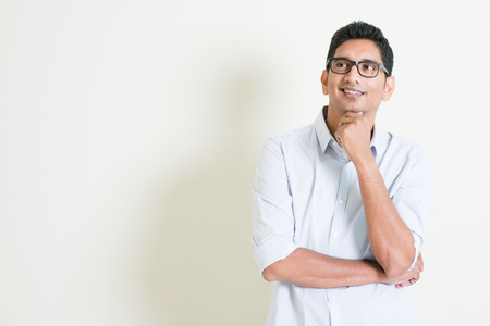 Foto de Portrait of handsome casual business Indian man smiling and thinking, eyes looking upwards, standing on plain background with shadow, copy space at side. - Imagen libre de derechos
