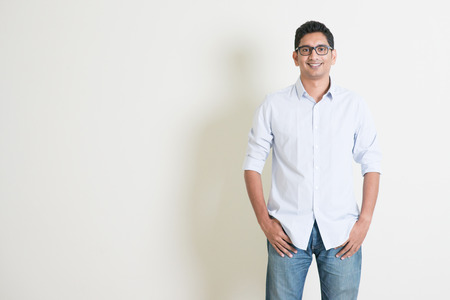 Photo for Portrait of handsome casual business Indian guy smiling, hands in pocket, standing on plain background with shadow, copy space at side. - Royalty Free Image