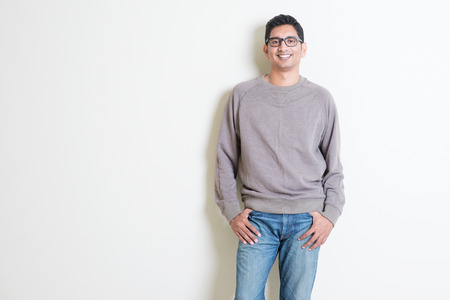 Photo for Portrait of handsome casual Indian male smiling, standing on plain background with shadow, copy space at side. - Royalty Free Image