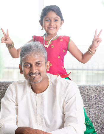 Happy Indian family at home. Asian girl showing peace hand sign. Adults and kids indoor lifestyle.