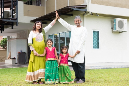 Parents forming house roof shape above children. Beautiful Asian Indian family portrait smiling and standing outside their new house.