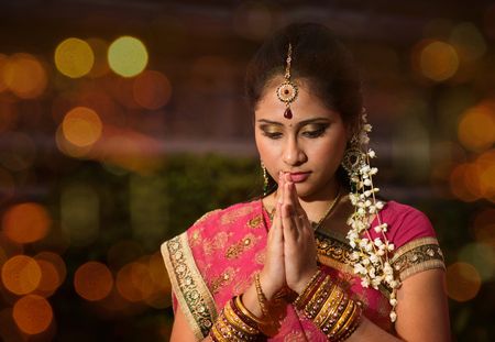Photo for Indian female in traditional sari praying and celebrating Diwali or deepavali, fesitval of lights at temple. Girl prayer hands folded, beautiful lights bokeh background. - Royalty Free Image