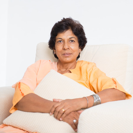 Foto für Portrait of a tired 50s Indian mature woman resting on sofa at home. Indoor senior people living lifestyle. - Lizenzfreies Bild
