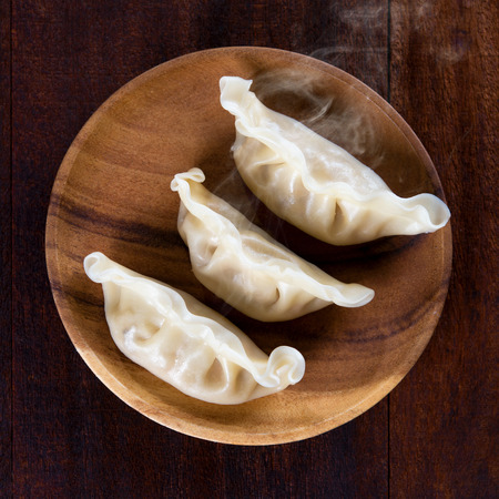 Top view close up fresh dumplings with hot steams on wood plate. Chinese food on rustic old vintage wooden background.