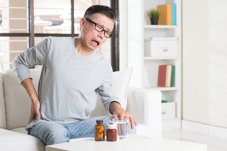 Foto de Portrait of casual 50s mature Asian man back pain, pressing on hip with painful expression, sitting on sofa at home, medicines and water on table. - Imagen libre de derechos