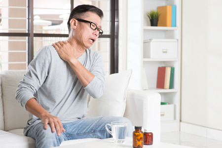 Photo pour Portrait of casual 50s mature Asian man shoulder pain, pressing on neck with painful expression, sitting on sofa at home, medicines and water on table. - image libre de droit