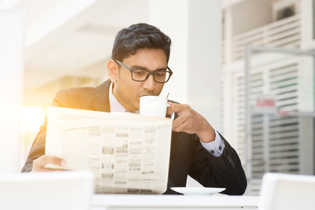 Foto de Young Asian Indian businessman sipping coffee and reading newspaper at cafe. India male business man, modern office building with beautiful golden sunlight as background. - Imagen libre de derechos
