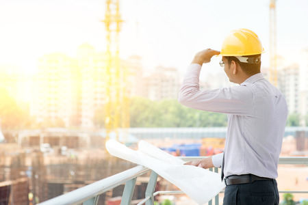 Foto de Asian Indian male site contractor engineer with hard hat holding blue print paper looking away inspecting at construction site, crane with golden sunlight at the background. - Imagen libre de derechos