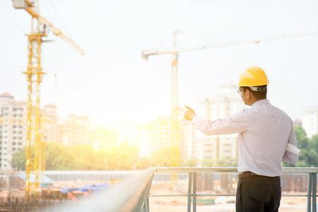 Foto de Asian Indian male site contractor engineer with hard hat holding blue print paper pointing at construction site, crane with golden sunlight at the background. - Imagen libre de derechos