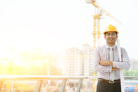 Photo pour Portrait of Asian Indian male site contractor engineer with hard hat holding blue print paper looking at camera and smiling at construction site, crane with golden sunlight at the background. - image libre de droit