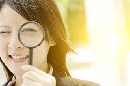 Photo for Young Asian business woman looking through magnifying glass, at an office environment, natural golden sunlight at background. - Royalty Free Image