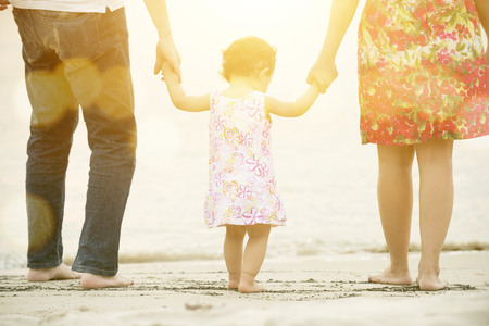 Photo for Happy Asian family outdoor activity, holding hands together walking on sand seaside in sunset during vacations. - Royalty Free Image