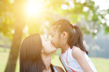 Lifestyle portrait mom and daughter kissing in happiness at the outside in the park. Family outdoor fun, morning with sun flare.