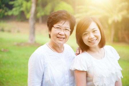 Photo for Portrait of attractive Asian elderly mother and daughter, senior adult woman and grown child. Outdoors family at nature park with beautiful sun flare. - Royalty Free Image