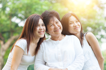 Foto de Portrait of happy Asian elderly mother and her daughters, senior adult woman and grown child. Outdoors family at nature park with beautiful sun flare. - Imagen libre de derechos