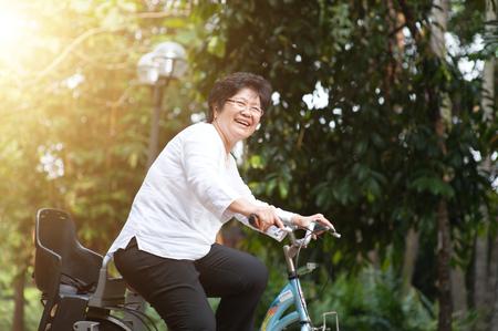 Photo pour Active elderly Asian woman cycling, senior adult activity, riding bike outdoor in morning. - image libre de droit
