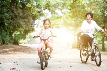 Foto de Portrait of active multi generations Asian family at nature park. Grandmother and granddaughter riding bicycle outdoor. Morning sun flare background. - Imagen libre de derechos
