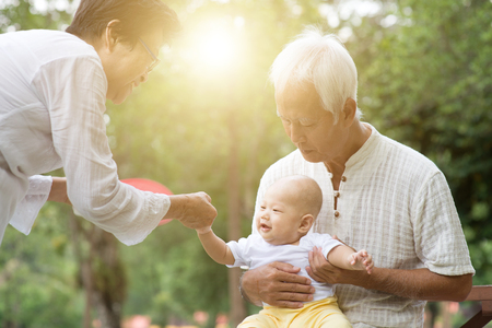 Photo for Baby grandson and grandparents having fun outdoors. Asian family, life insurance concept. - Royalty Free Image