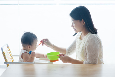 Photo for Happy Asian family at home. Mother feeding solid food to 9 months old toddler in the kitchen, living lifestyle indoors.  - Royalty Free Image
