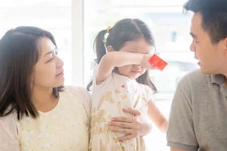 Foto de Parents comforting crying daughter. Asian family at home, natural living lifestyle indoors. - Imagen libre de derechos