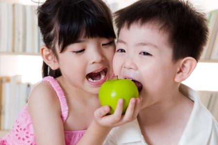 Foto de Asian kids sharing an apple - Imagen libre de derechos