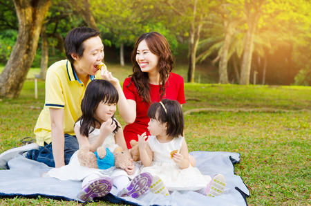 Photo pour Asian family picnic in the park - image libre de droit