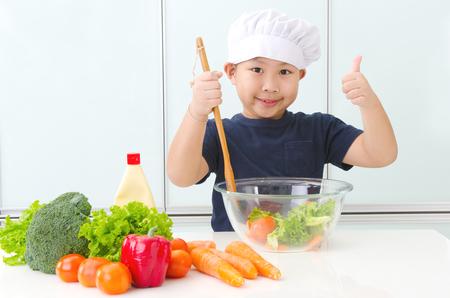 Foto de Asian boy preparing salad in the kitchen - Imagen libre de derechos