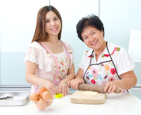 Photo pour Asian senior woman and daughter prepare for baking in the kitchen - image libre de droit